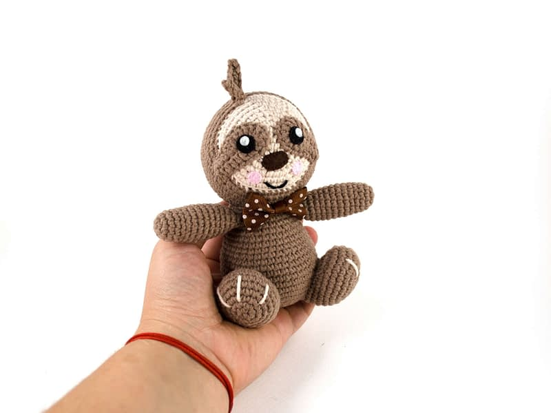 holding in hand little crochet sloth