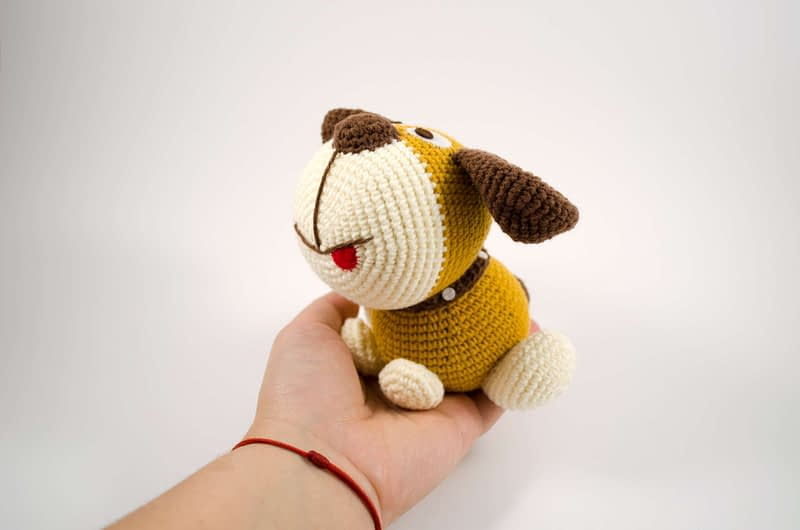 holding crochet puppy dog toy