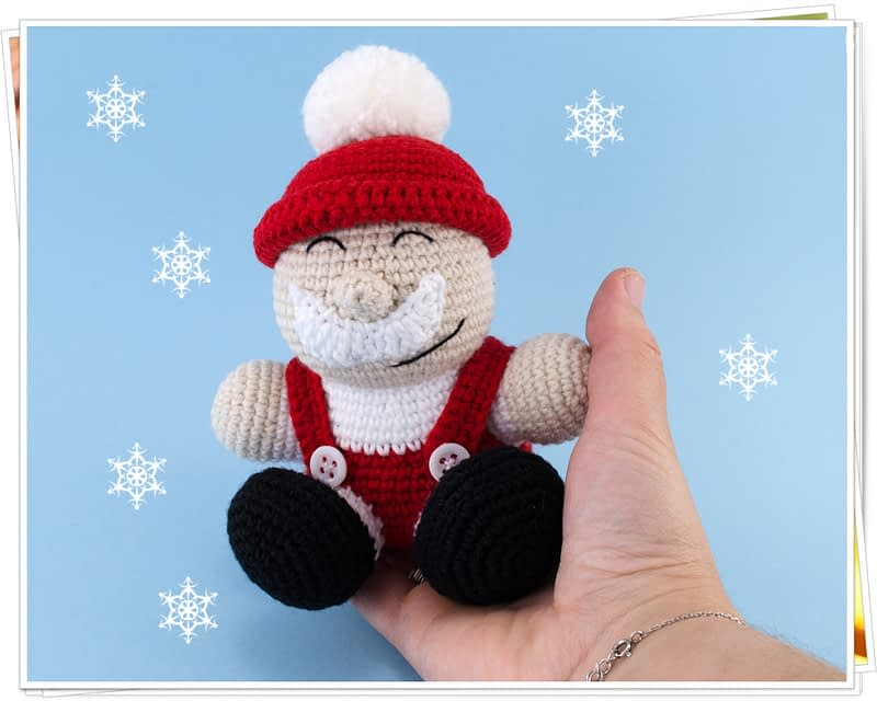 holding in hand crochet santa claus toy